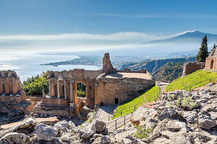 Greek theater of Taormina and smoking Etna in the background